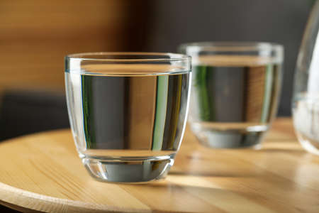 Glass of water on wooden table in room, closeup. Refreshing drink
