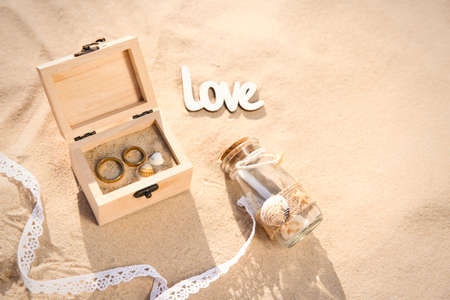 Wooden box with gold wedding rings, invitation in glass bottle and word Love on sandy beach