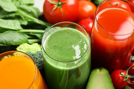 Delicious vegetable juices and fresh ingredients as background, closeup