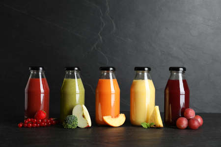 Bottles with delicious colorful juices and fresh ingredients on black table