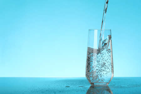 Pouring water into glass on blue background, space for text. Refreshing drink