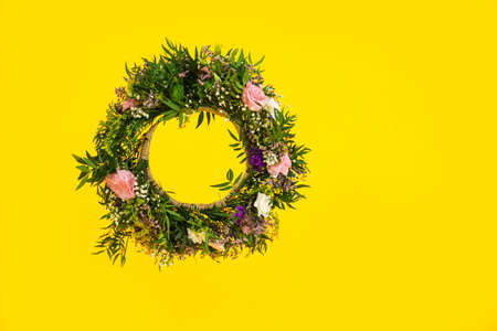 Wreath made of beautiful flowers hanging on yellow background. Space for text