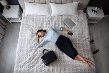 Exhausted businesswoman in office wear sleeping on bed at home after work, above view Stock Photo