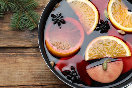 Delicious mulled wine on wooden table, top view