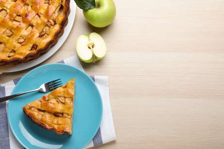 Traditional apple pie and fresh fruits on wooden table, flat lay. Space for text