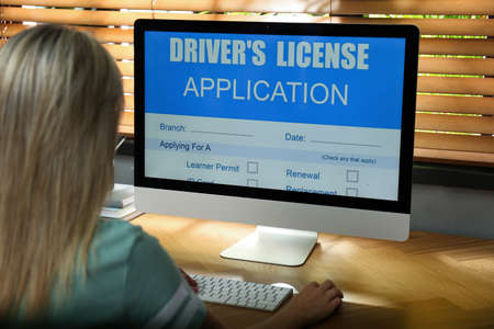 Woman using computer to fill driver's license application form at table in office, closeup