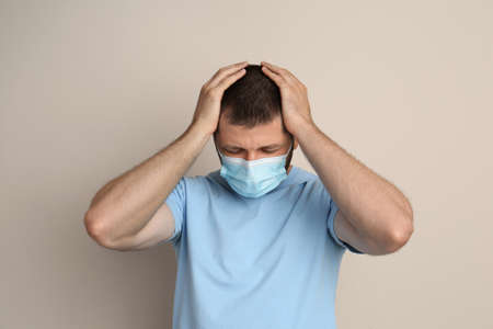 Stressed man in protective mask on beige background. Mental health problems during COVID-19 pandemic