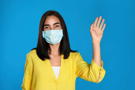 Young woman in protective mask showing hello gesture on light blue background. Keeping social distance during coronavirus pandemic