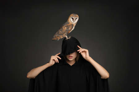 Witch in black mantle with owl on dark background. Scary fantasy character