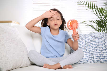 Little girl with portable fan suffering from heat at home. Summer season