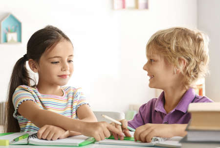 Little boy and girl doing homework at table indoors