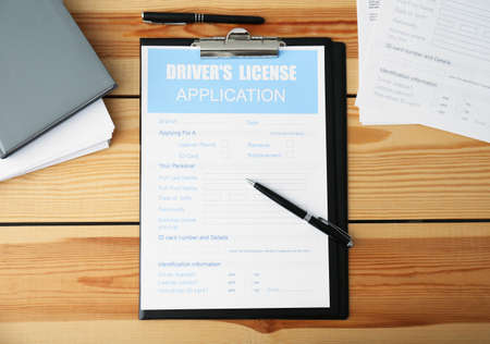 Driver's license application form, documents and stationery on wooden table, flat lay
