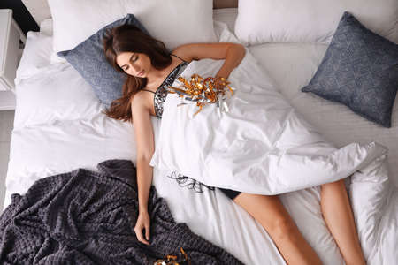 Exhausted woman in festive dress sleeping on bed at home after party, above view