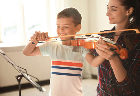 Young woman teaching little boy to play violin indoors