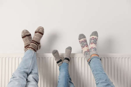 Family warming legs on heating radiator near white wall, closeup Reklamní fotografie