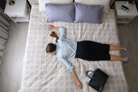 Exhausted businesswoman in office wear sleeping on bed at home after work, above view