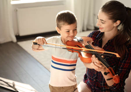 Young woman teaching little boy to play violin indoors Stockfoto