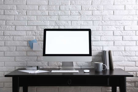 Comfortable workplace with modern computer on black table near white brick wall. Space for text