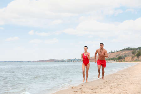 Professional lifeguards running at sandy beach on sunny day Stock Photo