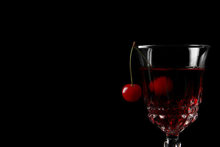 Delicious cherry wine with ripe juicy berries on black background, closeup. Space for text