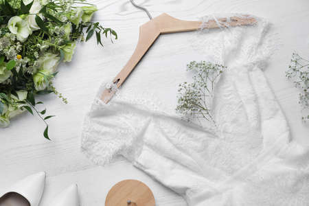 Beautiful wedding dress, engagement ring and flowers on white wooden background, flat lay Archivio Fotografico