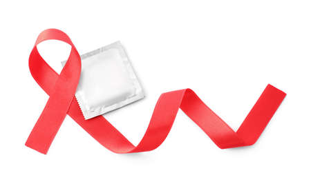 Red ribbon and condom isolated on white, top view. AIDS disease awareness Standard-Bild