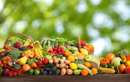Assortment of fresh organic vegetables and fruits on wooden table against blurred green background