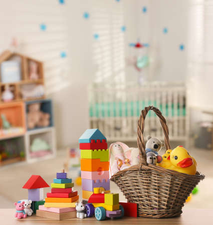Set of different cute toys on wooden table in children's room Standard-Bild
