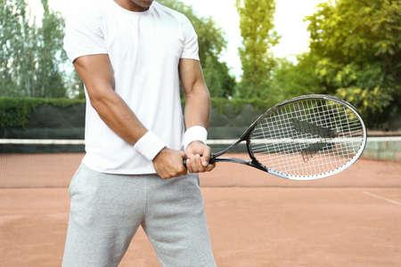 Sportsman playing tennis at court on sunny day, closeup Zdjęcie Seryjne