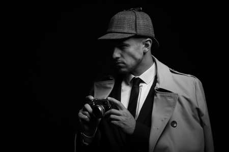 Old fashioned detective with camera on dark background, black and white effect. Space for text Archivio Fotografico