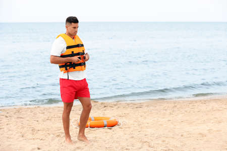 Handsome male lifeguard putting on life vest at sandy beach