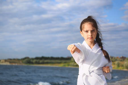Cute little girl in kimono practicing karate near river