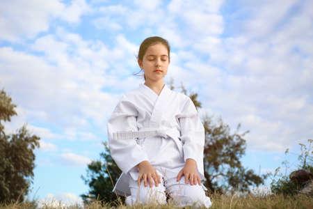 Cute little girl in kimono meditating outdoors. Karate practicing