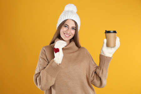 Happy beautiful woman with paper cup of mulled wine on yellow background