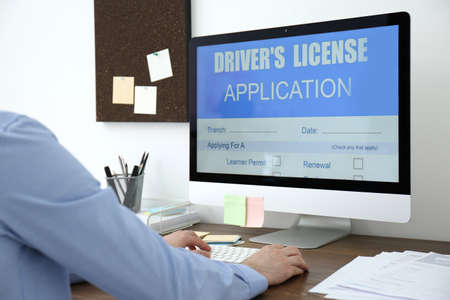 Man using computer to fill driver's license application form at table in office, closeup