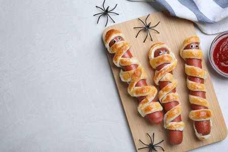 Cute sausage mummies served on white table, flat lay with space for text. Halloween party food