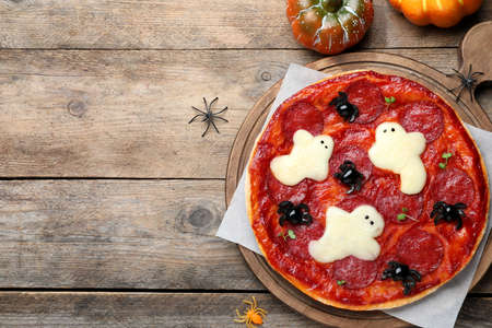 Cute Halloween pizza with ghosts and spiders served on wooden table, flat lay. Space for text
