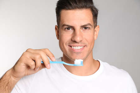 Man holding toothbrush with paste on light background Stok Fotoğraf
