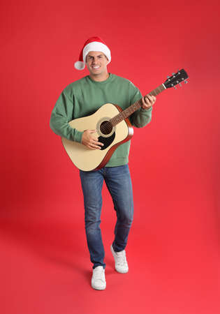 Man in Santa hat playing acoustic guitar on red background. Christmas music