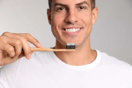 Man holding toothbrush with paste on light background, closeup Stok Fotoğraf