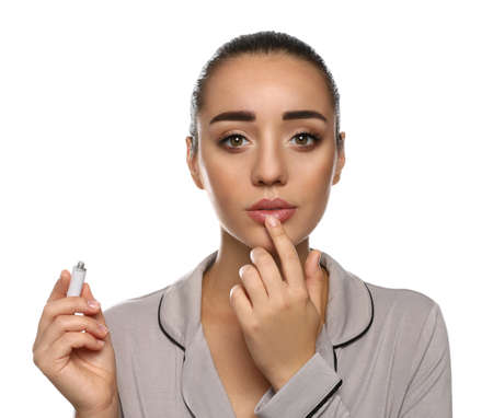 Woman with herpes applying cream on lips against white background