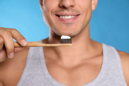 Man holding toothbrush with paste on blue background, closeup Stok Fotoğraf