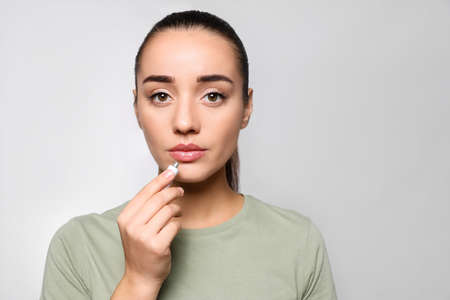 Woman with herpes applying cream on lips against light gray background. Space for text
