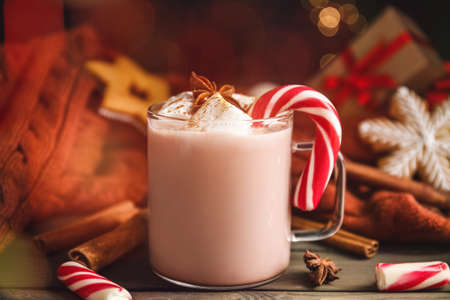 Glass cup of tasty cocoa with marshmallows and Christmas candy cane on wooden table Standard-Bild