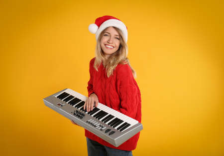 Young woman in Santa hat playing synthesizer on yellow background. Christmas music