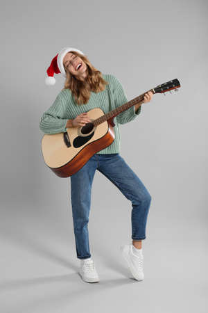 Young woman in Santa hat playing acoustic guitar on light gray background. Christmas music Stock Photo