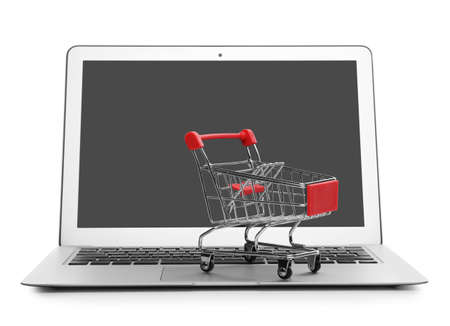 Internet shopping. Laptop with small cart isolated on white