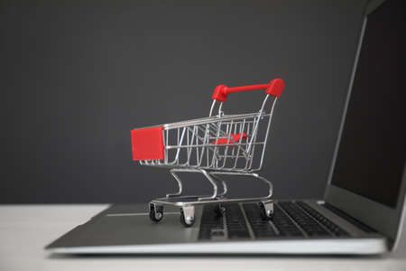 Internet shopping. Laptop with small cart on table against gray background