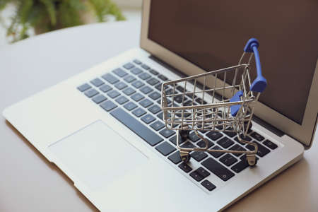 Internet shopping. Laptop with small cart on table indoors, closeup