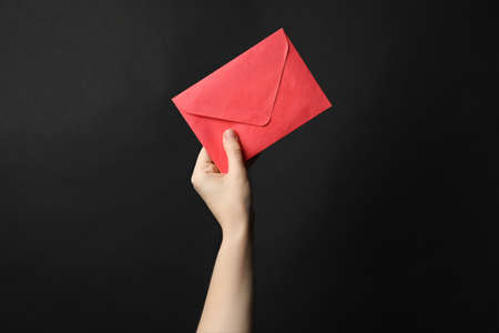 Woman holding red paper envelope on black background, closeup